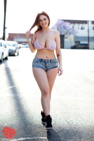 Curvy redhead in bikini top and denim shorts