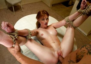 Hot redhead bound and fucked on a table
